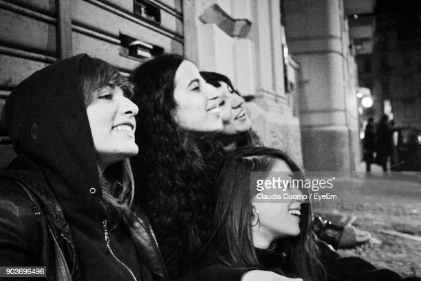 close-up of female friends smiling while sitting outdoors at night - cuomo stock pictures, royalty-free photos & images