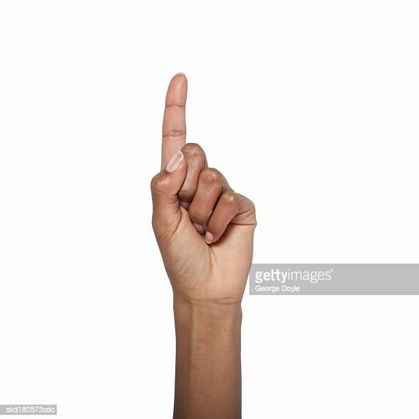 Close-up of female hand holding index finger up