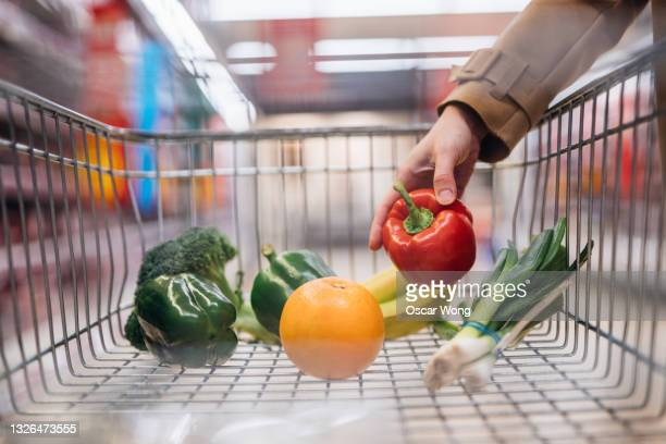 close-up of female hand placing fresh organic fruits and vegetables in shopping trolley - vegetable stock pictures, royalty-free photos & images