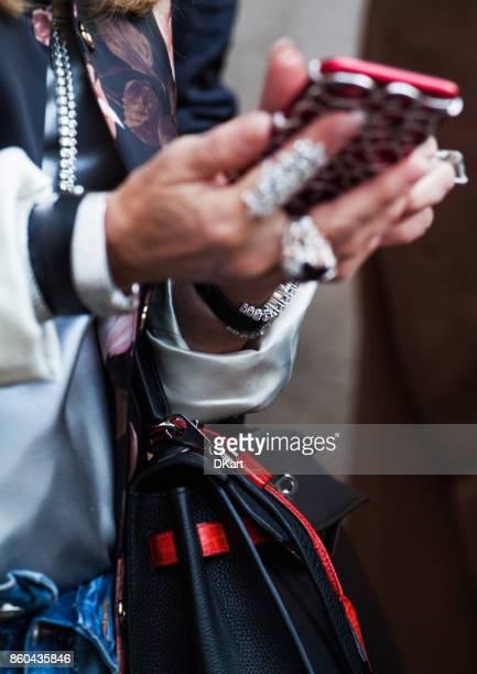 nahaufnahme von weiblichen händen in diamant-schmuck halten sie eine telefon in teure felge - fashion week stock-fotos und bilder