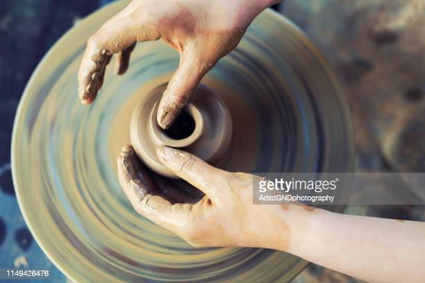close-up of female hands working on pottery wheel. - potter stock pictures, royalty-free photos & images