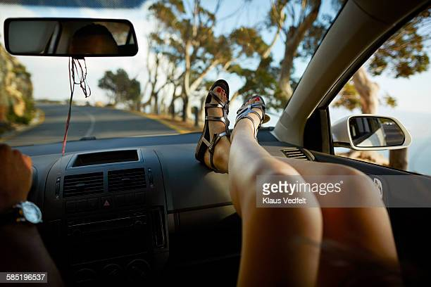 Close-up of female legs relaxing in car driving