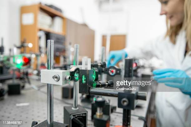 close-up of female researcher assembling laser experimentation platform part - laser stock pictures, royalty-free photos & images
