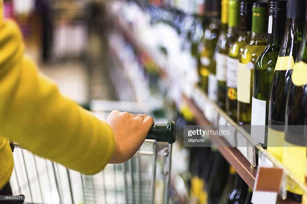 Closeup of female shopper with trolley at supermarket : Stock Photo