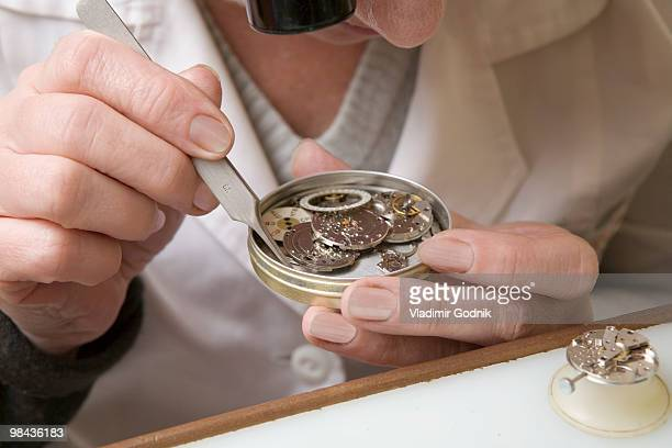 close-up of female watchmaker at work