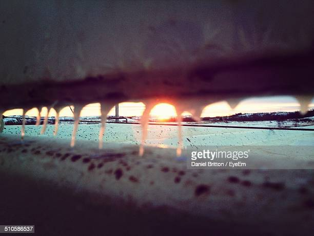 Close-up of fence with icicles during sunset