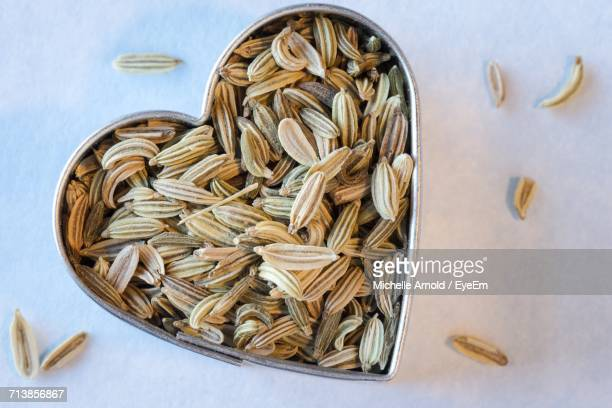 Close-Up Of Fennel Seeds In Heart Shape Container On Table