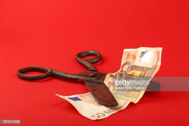 Close-Up Of Fifty Euro Banknote Cut With Old Scissors Against Red Background