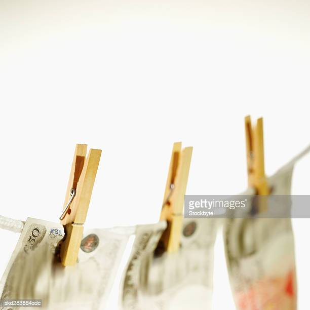 Close-up of fifty pound notes hanging on clothesline