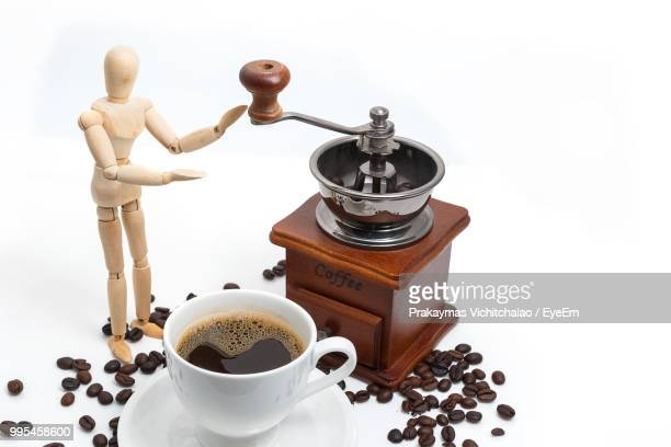 Close-Up Of Figurine By Coffee Grinder And Drink Against White Background