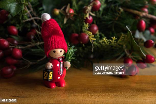 Close-Up Of Figurine On Table By Christmas Decoration