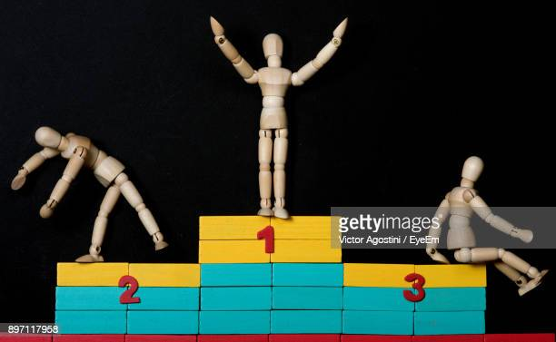 close-up of figurine on winners podium against black background - winners podium stock pictures, royalty-free photos & images