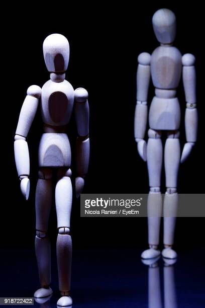 Close-Up Of Figurines Against Black Background