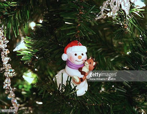 Close-Up Of Figurines Hanging On Christmas Tree