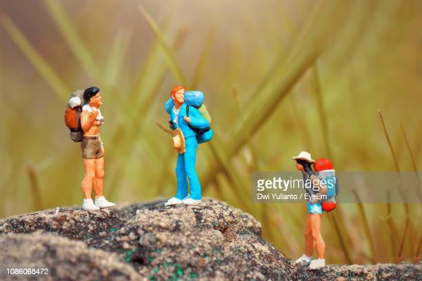 close-up of figurines hiking on rock - human representation stock pictures, royalty-free photos & images