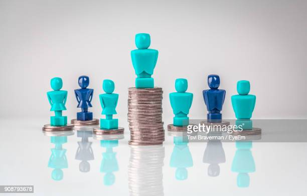 close-up of figurines on coins over table - wage gap stock pictures, royalty-free photos & images