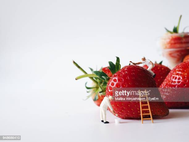 Close-Up Of Figurines Strawberry Over White Background