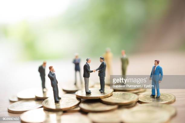 close-up of figurines with coins on wooden table - human representation stock pictures, royalty-free photos & images