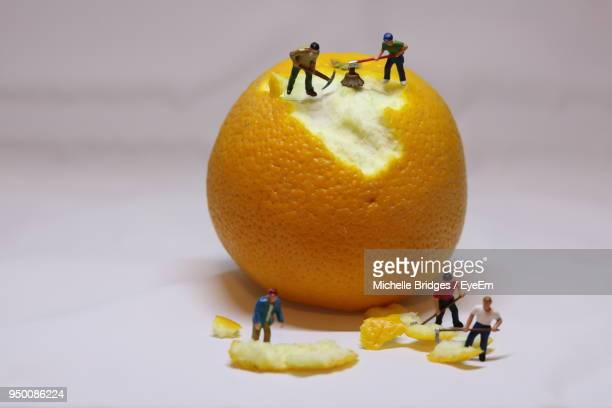 close-up of figurines with orange against white background - human representation stock pictures, royalty-free photos & images