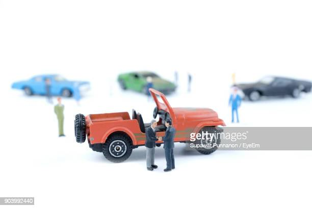 Close-Up Of Figurines With Toy Cars Against White Background