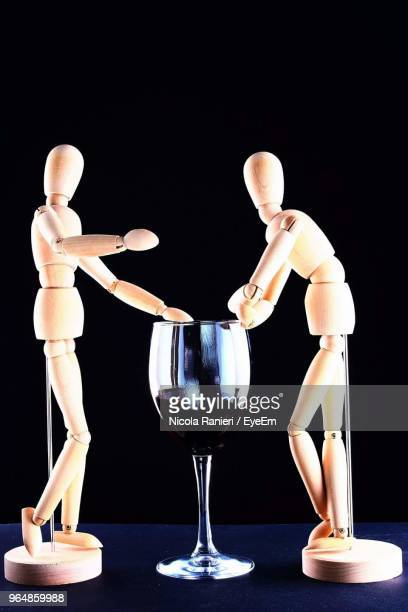 Close-Up Of Figurines With Wineglass On Table Against Black Background