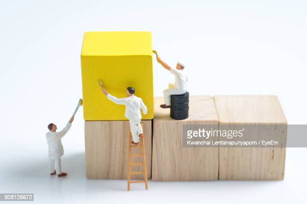 Close-Up Of Figurines With Wooden Blocks Against White Background
