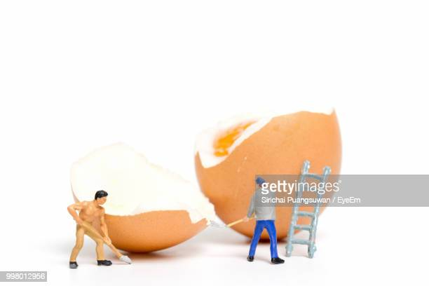 Close-Up Of Figurines Working With Eggs On White Background