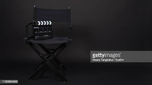 close-up of film slate with chair against black background - clapboard stock pictures, royalty-free photos & images