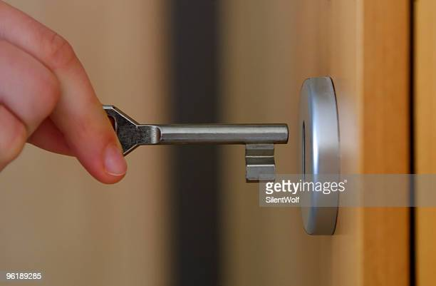 Close-up of fingers inserting a key into a door lock