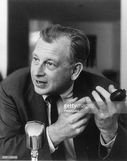 Closeup of FinnishAmerican architect and industrial designer Eero Saarinen a pipe in one hand as he talks into a microphone 1958