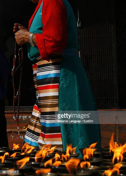 Close-Up Of Fire Against Woman With Religious Beads