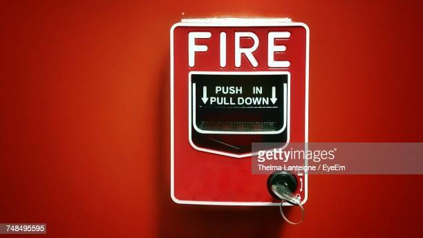 Close-Up Of Fire Alarm Box On Red Wall