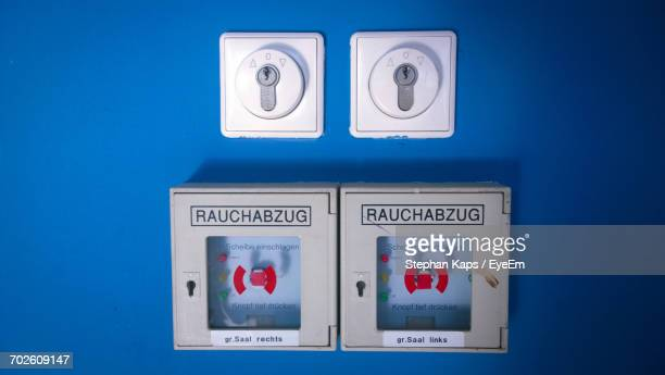 Close-Up Of Fire Alarms Mounted On Blue Wall