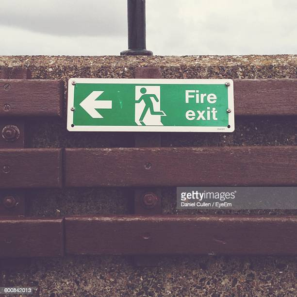 Close-Up Of Fire Exit Sign On Surrounding Wall
