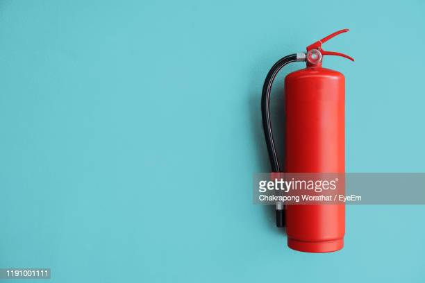 close-up of fire extinguisher against blue background - 消火器 ストックフォトと画像