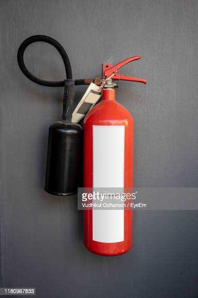 close-up of fire extinguisher against wall - 消火器 ストックフォトと画像