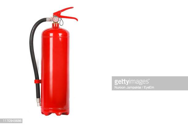 close-up of fire extinguisher against white background - objet rouge photos et images de collection