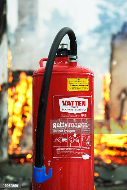Close-up of fire extinguisher, flames in background