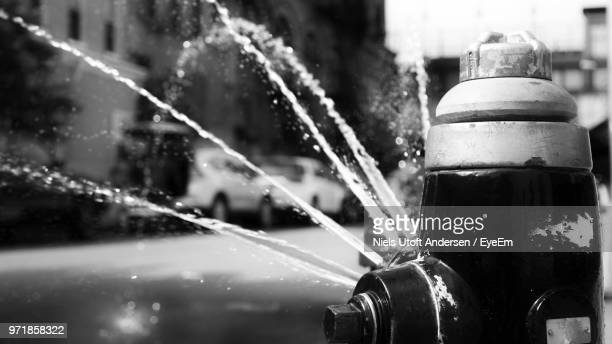 close-up of fire hydrant by splashing water - fire hydrant stock pictures, royalty-free photos & images