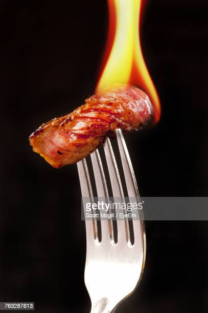 Close-Up Of Fire On Meat In Fork Against Black Background