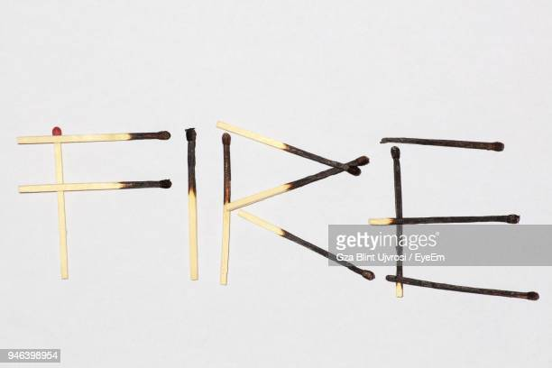 Close-Up Of Fire Text Made From Matchsticks Against White Background
