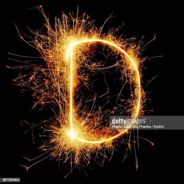 close-up of firework display against black background - letter d stock pictures, royalty-free photos & images