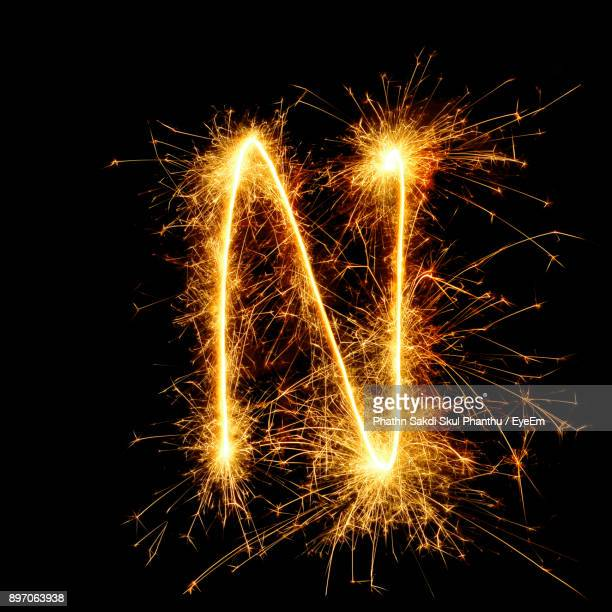 close-up of firework display against black background - letter n stock pictures, royalty-free photos & images