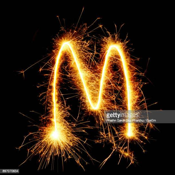 close-up of firework display against black background - letter m stock pictures, royalty-free photos & images