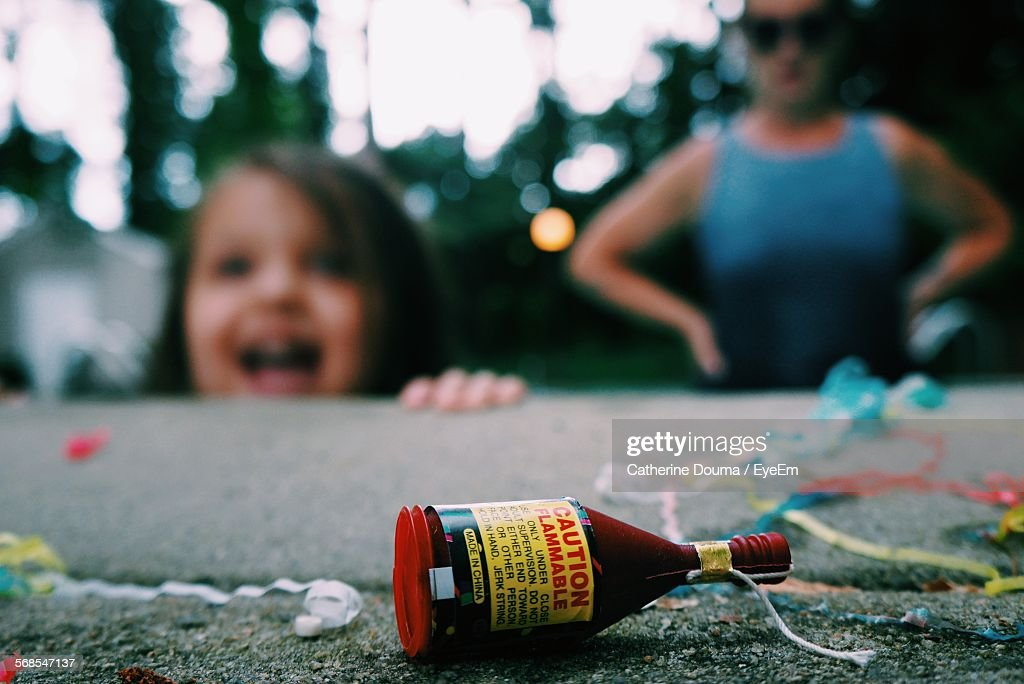 Close-Up Of Firework In Bottle On Retaining Wall With People In Background : Stock Photo
