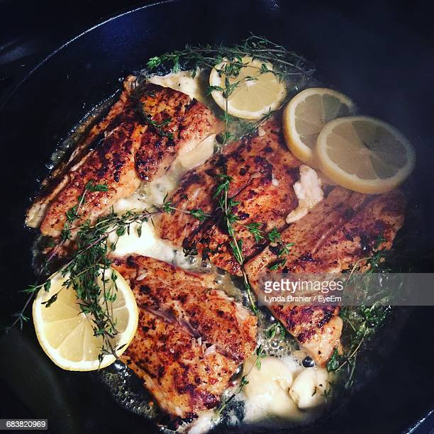 Close-Up Of Fish Cooking In Pot With Herbs And Lemon
