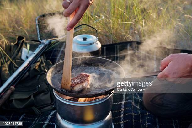 close-up van visser koken haar vangst op het strand - nordic combined stockfoto's en -beelden