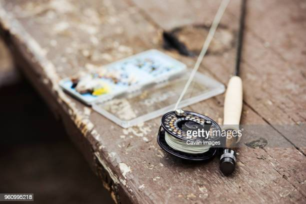 Close-up of fishing rod and hooks on wooden table outdoors
