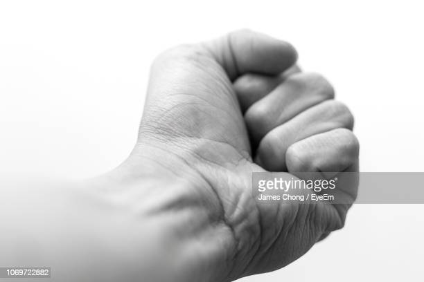 Close-Up Of Fist Against White Background