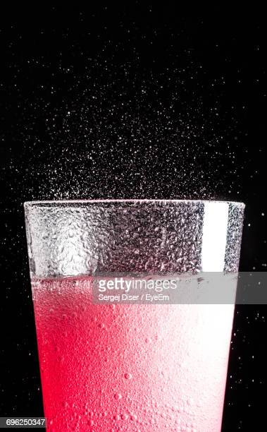 Close-Up Of Fizzy Drink Against Black Background